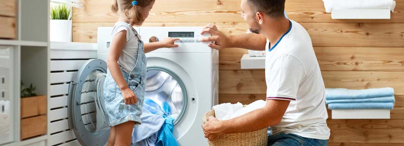 Father and child daughter doing laundry together in a fun kids laundry time