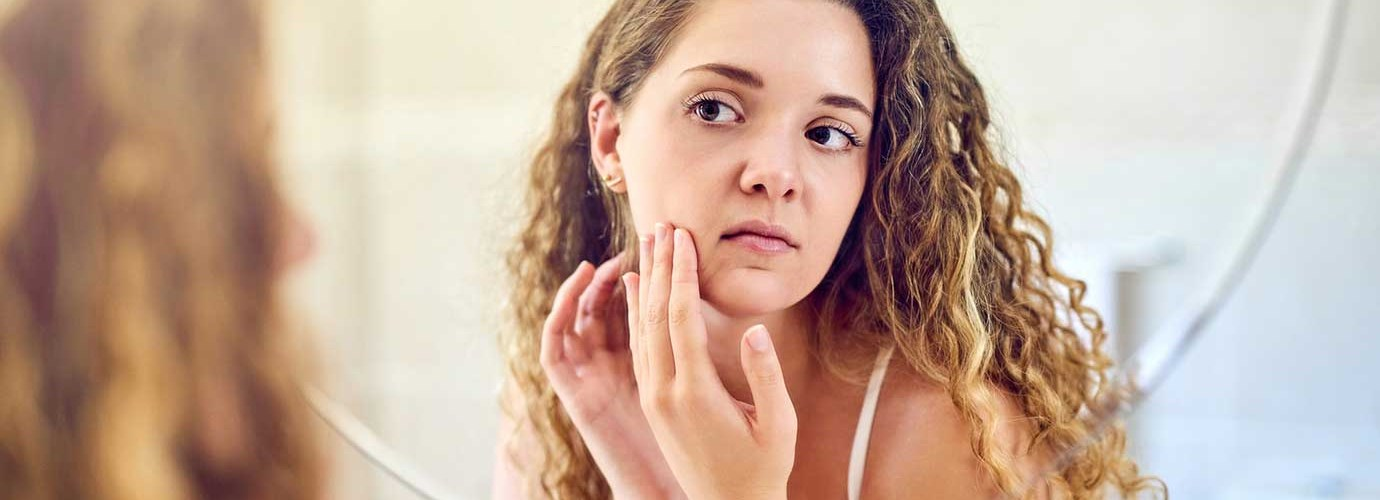 A young woman squeezing a pimple on her oily skin and looking at the mirror