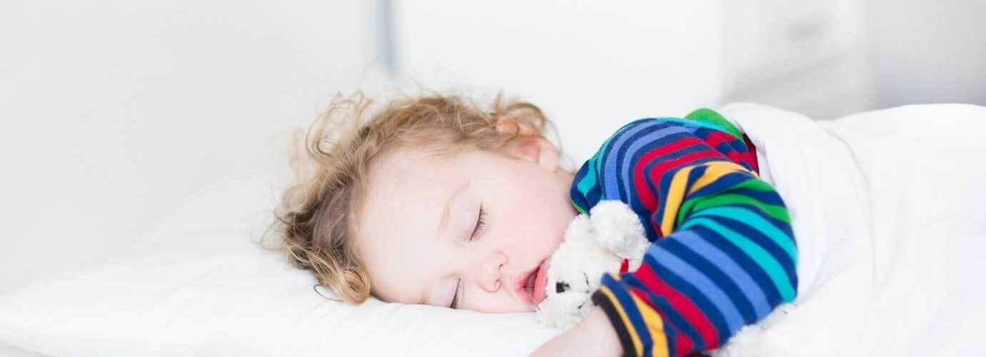 Toddler girl sleeping on a bed