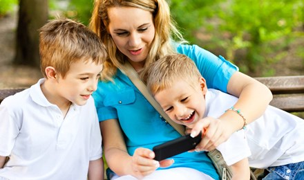 A woman sitting in the middle of two young boys showing them something on her phone