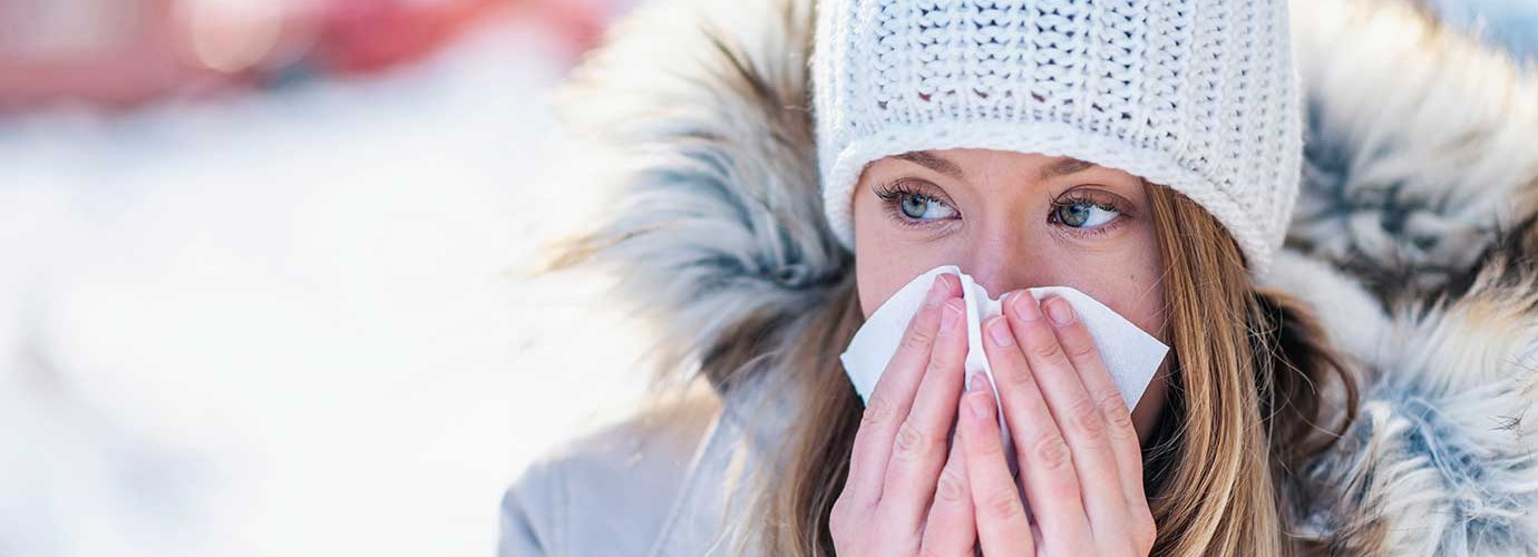Woman in the snow blowing her nose