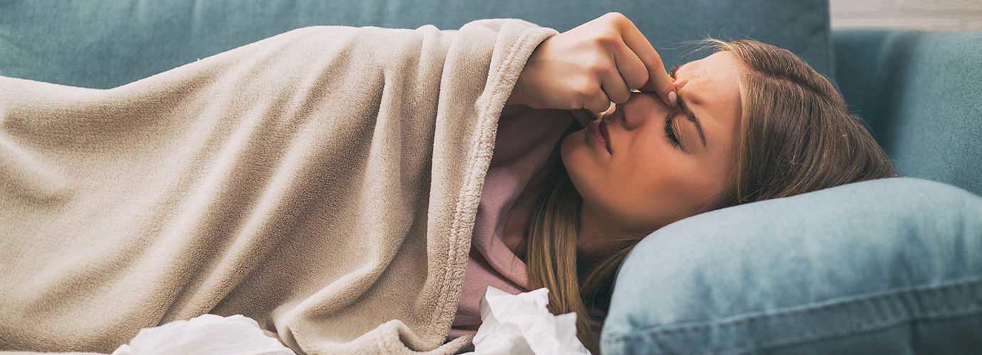 Woman lying in a blue sofa feeling sinus pain