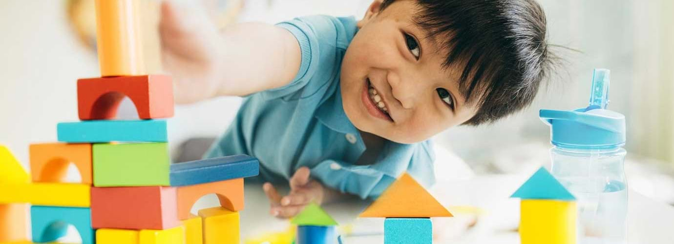 A young boy playing with colourful wooden toys